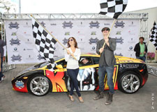 Hayden Christensen and Eva Longoria Parker wave the checkered flags to signal drivers to start their engines in the Rally for Kids with Cancer.