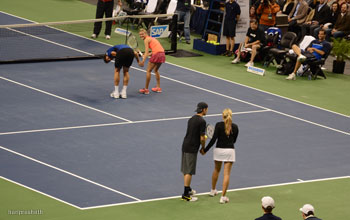 Hayden Christensen gets ready to toss the ball while holding hands with Aleksandra Wosniak for her serve in mixed doubles match November 17, 2011 tennis.